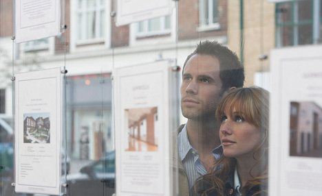 AG2J0G Couple Looking in Real Estate Agent's Window
